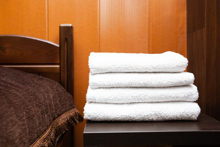 A stack of clean white towels lies on a bedside table in a hotel room. Room cleaning. Travel concept.