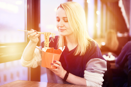 Girl eat wok on food kurt. Beautiful woman eating thai noodles in paper box takeaway. Image with gold sunlight flare copyspace for text and design.