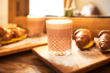 Original authors coffee on beet milk and fresh croissant with fruits on wooden plate on table. Healthy breakfast food concept. Traditional french lunch in morning cafe with gold sunlight flare.