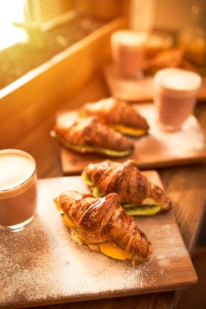 Fresh croissant and original authors coffee on beet milk with fruits on wooden plate on table. Healthy breakfast food concept. Traditional french lunch in morning cafe with gold sunlight flare. Archivio Fotografico