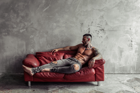 Fashion portrait of Sexy naked male model with tattoo and a black beard lying in hot pose on red leather sofa. Loft room interior with grey concrete wall. Professional Studio image. Banco de Imagens