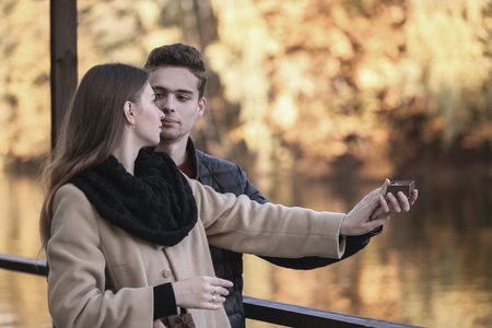 The guy makes a proposal to the girl. A young loving couple is standing in the autumn park with yellow trees. A man holds a box with a ring. Woman says No. Reklamní fotografie