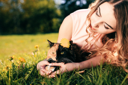 Girl lying on grass with cat. Spring or summer warm weather concept. Bokeh background. Ginger kitten with two face color mask. Reklamní fotografie