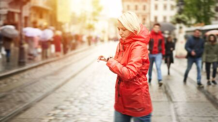 Time concept. Girl looking on watch and waiting friend on the street. Portrait of pretty smiling young woman in red bright raincoat. Web 16 in 9 crop banner size image with flare. 스톡 콘텐츠