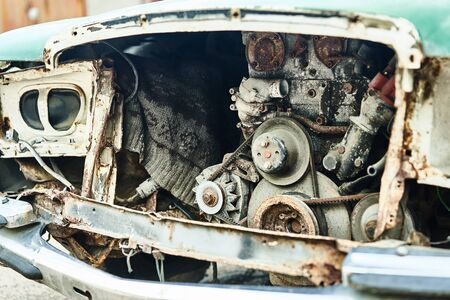 Details of old car. Aged oldtimer vintage automobile. Spare parts of retro classic automobile. Disassembled car in a parking lot. Stock Photo