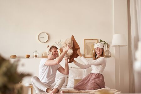 Pair in love laughing and playing on bed. Man and woman fight pillows. Young happy couple beat the pillows on the bed in a bedroom at home. Standard-Bild