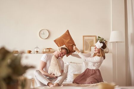 Pair in love laughing and playing on bed. Man and woman fight pillows. Young happy couple beat the pillows on the bed in a bedroom at home. Banque d'images
