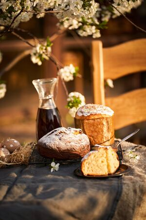 Traditional russian Easter cottage cheese dessert. Orthodox paskha, kulich cakes on table. Flowers bokeh background. Archivio Fotografico