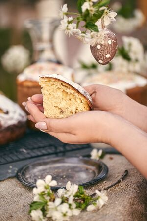 Traditional russian Easter cottage cheese dessert. Woman hands take a piece of orthodox paskha. Kulich cakes on table. Flowers bokeh background.