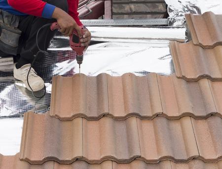 trussing: builder roofer lavorando con un cacciavite a costruzione di copertura Archivio Fotografico