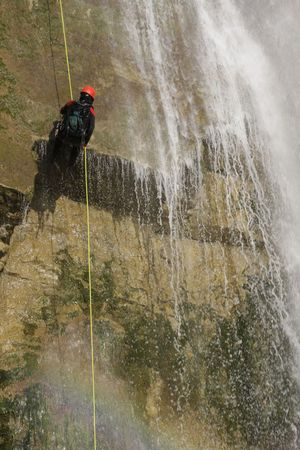 rappelling: a man rappelling in a waterfall