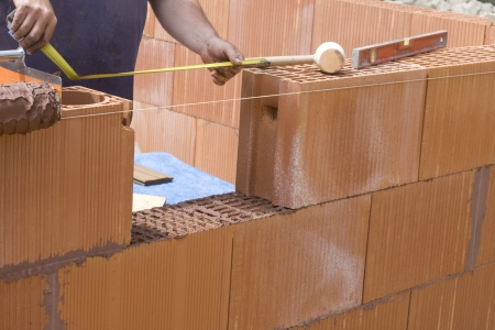 bricklayer: mason made a wall with red bricks Stock Photo