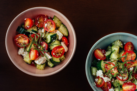 Ceramic bowls of Mediterranean Greek salad with cherry tomatoes, cucumber, feta cheese, extravirgin olive oil and black pepper