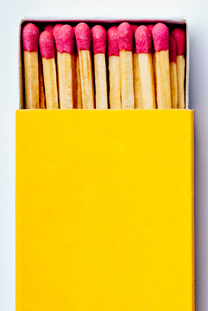 Brand new open yellow matchbox with many pink match sticks in it