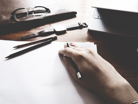 consist: The picture of hands working action on wooden table, consist of laptop, paper, pencil, watch, glasses, soft tone color Stock Photo