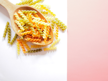 Its time for pasta dish, top view picture of multicolored uncooked fusilli consist of yellow, orange and green on wooden spoon above white and pink  background.