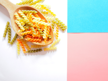 Its time for pasta dish, top view picture of multicolored uncooked fusilli consist of yellow, orange and green on wooden spoon above white, blue and pink  background.