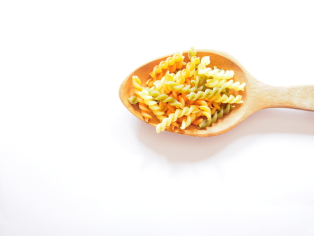 Its time for pasta dish, top view picture of multicolored uncooked fusilli consist of yellow, orange and green on wooden spoon above  white background.
