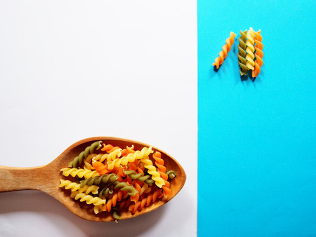 Its time for pasta dish, top view picture of multicolored uncooked fusilli consist of yellow, orange and green on wooden spoon above white and blue  background.