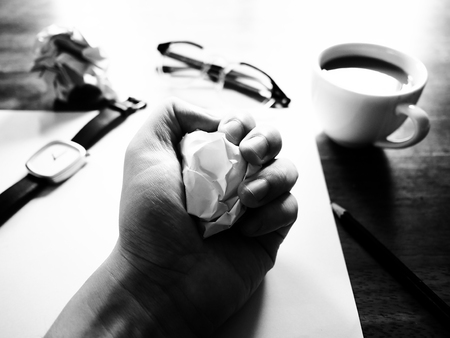 failed plan: Businesses have both been successful and fail. The picture of fail work, glasses, paper, pencil, watch, a cup of coffee  and men hand gesture above wooden table. selective focus.  black and white color