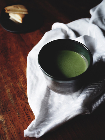 tea hot drink: The picture of a cup of matcha latte and custard cake on white fabric above old  wooden texture.