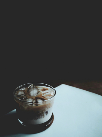 vaso de precipitado: The picture of iced coffee in the glass on black background. selective focus,  soft tone style