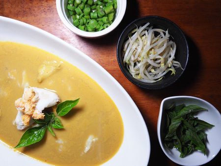 long bean: Top view picture of Thai curry crab on white dish above wooden table served with boiled Thai basil, boiled long bean sliced and boiled Sprout. Stock Photo