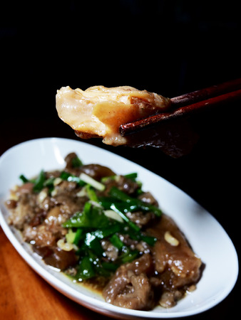 The picture of stir fried beef stew with green peppers on white dish, black background. selective focus