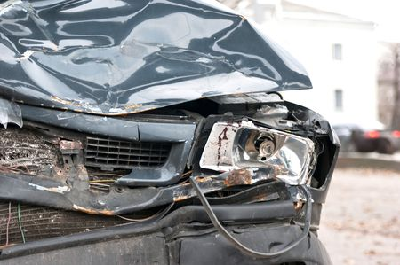 A wrecked car lays in wait after a vicious car accident photo