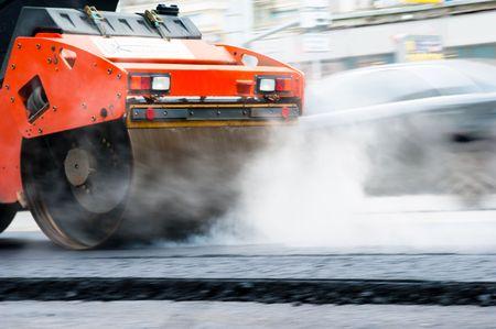 construction vehicle: Steamroller compressing asphalt on a new road construction site