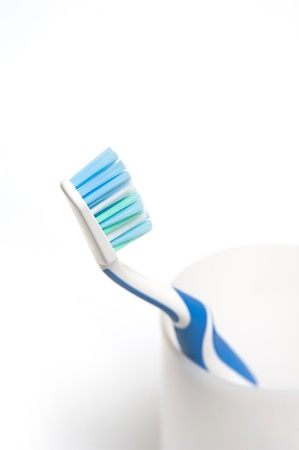 Blue toothbrush in glass. Focus is pointed at the bristle brushes