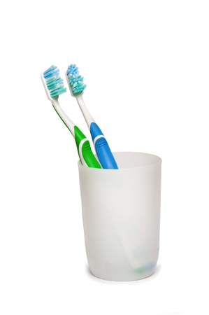 bristle: Two toothbrushes in glass.  Focus is pointed at the bristle brushes Stock Photo
