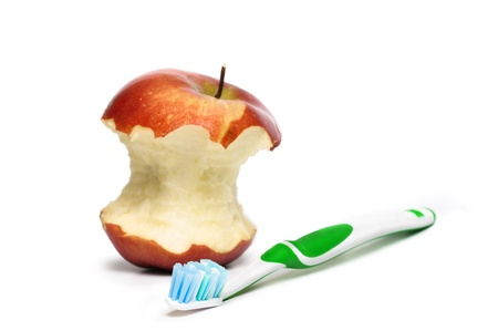 bristle: A toothbrush and an apple in the background. Focus is pointed at the bristle brush