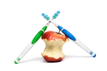 Two  toothbrushes and an apple on a white background Фото со стока
