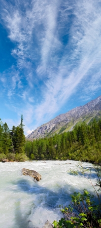 Turbulent Mountain River under Beautiful Blue Cloudy Sky photo