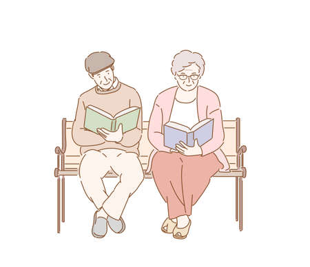 An elderly couple is sitting on a bench and reading a book.