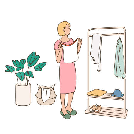 A woman is choosing clothes from hangers in a wardrobe.