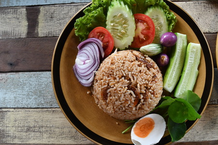 Thai style food ,  fired rice with shimps and fresh vegetables lay on plate