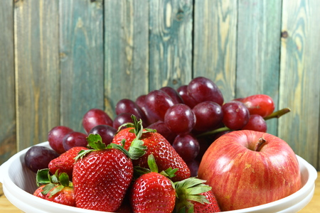 Red fruits on the wood background Imagens