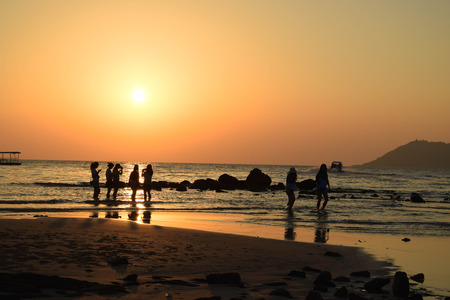 People walking on the beach in sunset