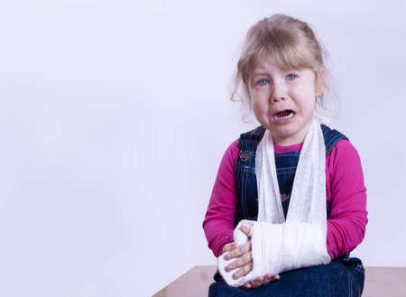 el ni�o con el brazo roto en un llanto yeso Foto de archivo - 16714001