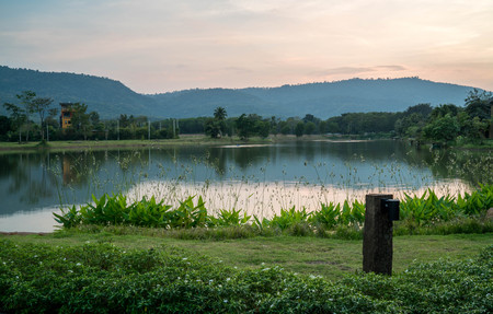 Reflective pond on the mountain surrounded by green grass and garden