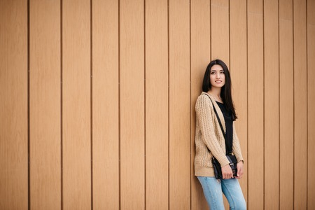 nicely: Stylish woman smiling stands near a wooden wall.