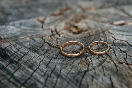 weddingrings: Beautiful wedding rings on wooden background, a stump