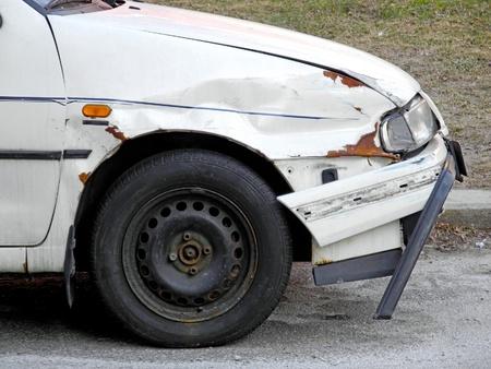 Weggegooid en beschadigd wrak van auto met gebroken bumper Stockfoto