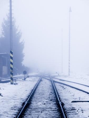 Perspectief van spoorweg in de winter smog