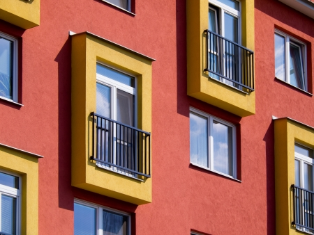 Detail of modern apartments with balconies and red walls Stock Photo