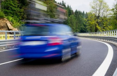 Fast blurred blue car on a twisty mountain road photo