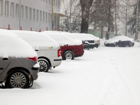 Snowy cars parked in a parking lots during blizzard Stock Photo