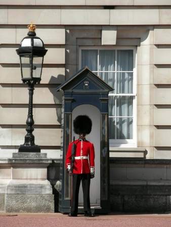 Queen Guard standing before the Buckingham Palace in London photo